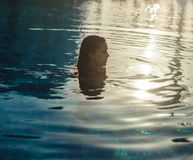 Girl swimming in the pool with eyes squinting. Head is out of water Stock Images