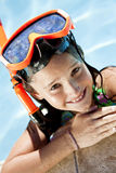Girl In A Swimming Pool with Goggles and Snorkel. A happy young girl smiling and relaxing on the side of a swimming pool wearing orange goggles and snorkel Stock Image