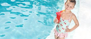 Girl in the swimming pool. Little girl in the swimming pool with cocktail Royalty Free Stock Images