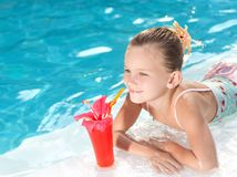 Girl in the swimming pool. Little girl in the swimming pool with cocktail Stock Photo