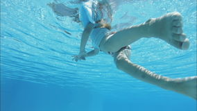 Girl swimming in pool. Little girl swimming in pool, view from underwater stock footage
