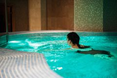 The girl is swimming in the pool. stock photography
