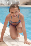 Girl by the swimming pool. Smiling little girl by the swimming pool Stock Photos