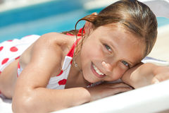 Girl by the swimming pool. Smiling little girl by the swimming pool Stock Photo