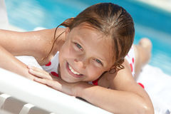 Girl by the swimming pool. Smiling little girl by the swimming pool Stock Image