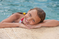 Girl by the swimming pool. Smiling little girl by the swimming pool Stock Photography