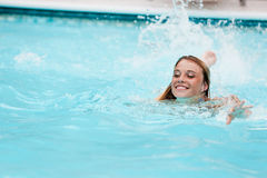 Girl swimming in pool. Smiling girl swimming in pool on sunny day Royalty Free Stock Photography