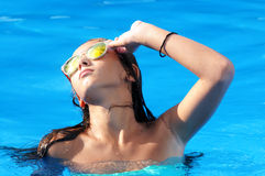 Girl in a swimming pool with sunglasses Royalty Free Stock Photo