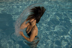 Girl in a swimming pool throwing wet hair. Attractive fit young tanned girl throwing wet hair back in swimming pool Royalty Free Stock Photography