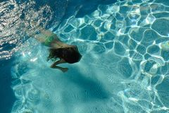 Girl swimming in a pool under water Royalty Free Stock Images