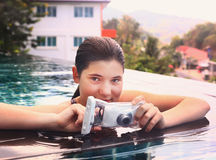 Girl  in swimming pool with underwater camera. Teenager girl i in water in swimming pool with camera in protective waterproof slipcover cover for underwater Stock Images