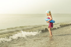 Girl with swimming ring playing on the beach Stock Photography