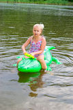 Girl swimming in the river with inflatable crocodile Royalty Free Stock Image