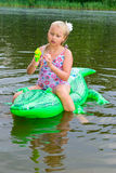 Girl swimming in the river with inflatable crocodile Royalty Free Stock Images