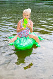 Girl swimming in the river with inflatable crocodile Stock Photo