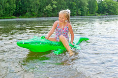 Girl swimming in the river with inflatable crocodile Stock Image