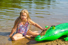 Girl swimming in the river with inflatable crocodile Stock Photos