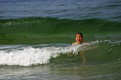 Girl swimming in sea. Young girl swimming through waves in sea Royalty Free Stock Images