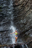 Girl in swimming suit standing under waterfall royalty free stock images