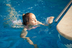 Girl swimming to the edge of swimming pool Stock Photo