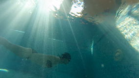 Girl swimming under water against the light in the pool stock video footage