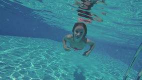 The girl swimming under the water stock video