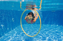 Girl swimming underwater in pool Stock Photos
