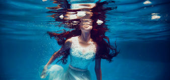 Girl swimming underwater Stock Image