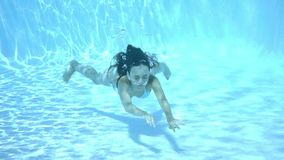 Girl swimming underwater in a swimming pool stock video footage