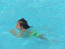 A girl swims in blue water Royalty Free Stock Images
