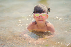 A girl swims and dives to the sea. Little girl swims and dives to the sea Stock Images