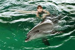A girl swims with a dolphin in the pool, communication with animals. Bright emotion royalty free stock photography