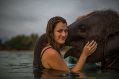Girl swims with the elephant Stock Photo