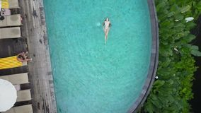 Girl swims in the pool. Aerial view stock footage