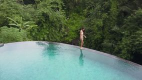 Girl swims in the pool. Aerial view stock video