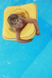 Girl swims in a pool with a circle Stock Image