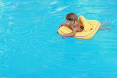 Girl swims in a pool with a circle Stock Images
