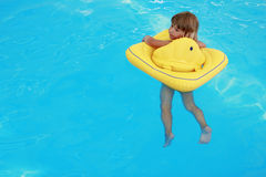 Girl swims in a pool with a circle Royalty Free Stock Photography