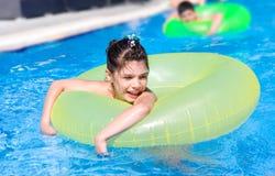 Girl swims in pool in circle Stock Photo