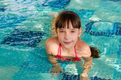 Girl swims in the pool. royalty free stock photography
