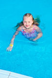 Girl swims in the pool. On a hot sunny day royalty free stock photography