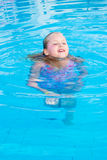Girl swims in the pool. On a hot sunny day stock photography