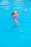 Girl swims in the pool. On a hot sunny day royalty free stock photo
