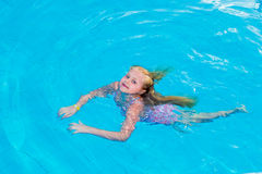 Girl swims in the pool. On a hot sunny day royalty free stock image
