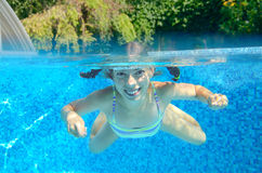 Girl swims in swimming pool, underwater and above view Royalty Free Stock Photos