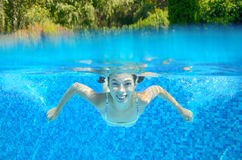 Girl swims in swimming pool, underwater and above view Royalty Free Stock Photography