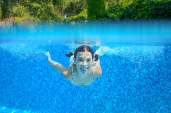 Girl swims in swimming pool, underwater and above view Stock Photo
