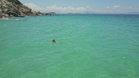 Girl Swims to Seacoast against Boundless Azure Ocean. Girl swims to seacoast in beautiful boundless azure ocean against distant hills on horizon under sunlight stock video