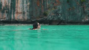 Girl swims in turquoise ocean`s water.  stock footage