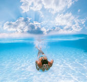 Girl swims under water in the pool Royalty Free Stock Photography